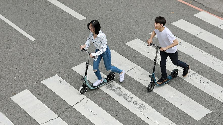 personnes faisant de la patinette sur un passage piéton